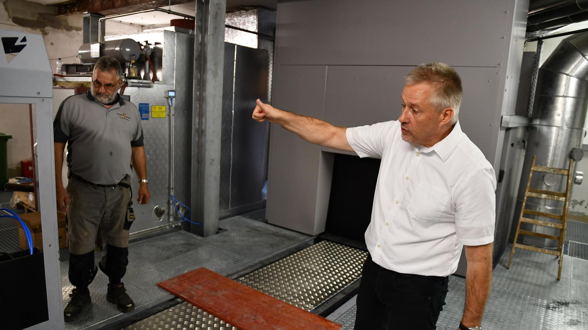 Ein Mann in weißem Hemd zeigt eine Abwärtsbewegung mit dem Daumen. Ein zweiter Mann schaut zu. Im Hintergrund befindet sich der neue Ofen des Krematoriums.