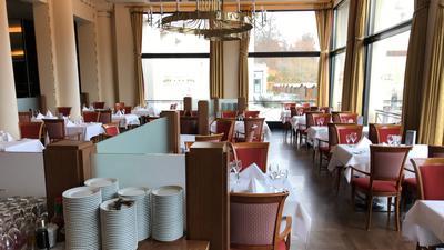 Weiß eingedeckte Tische und rote Polsterstühle stehen im Kurhaus-Restaurant.