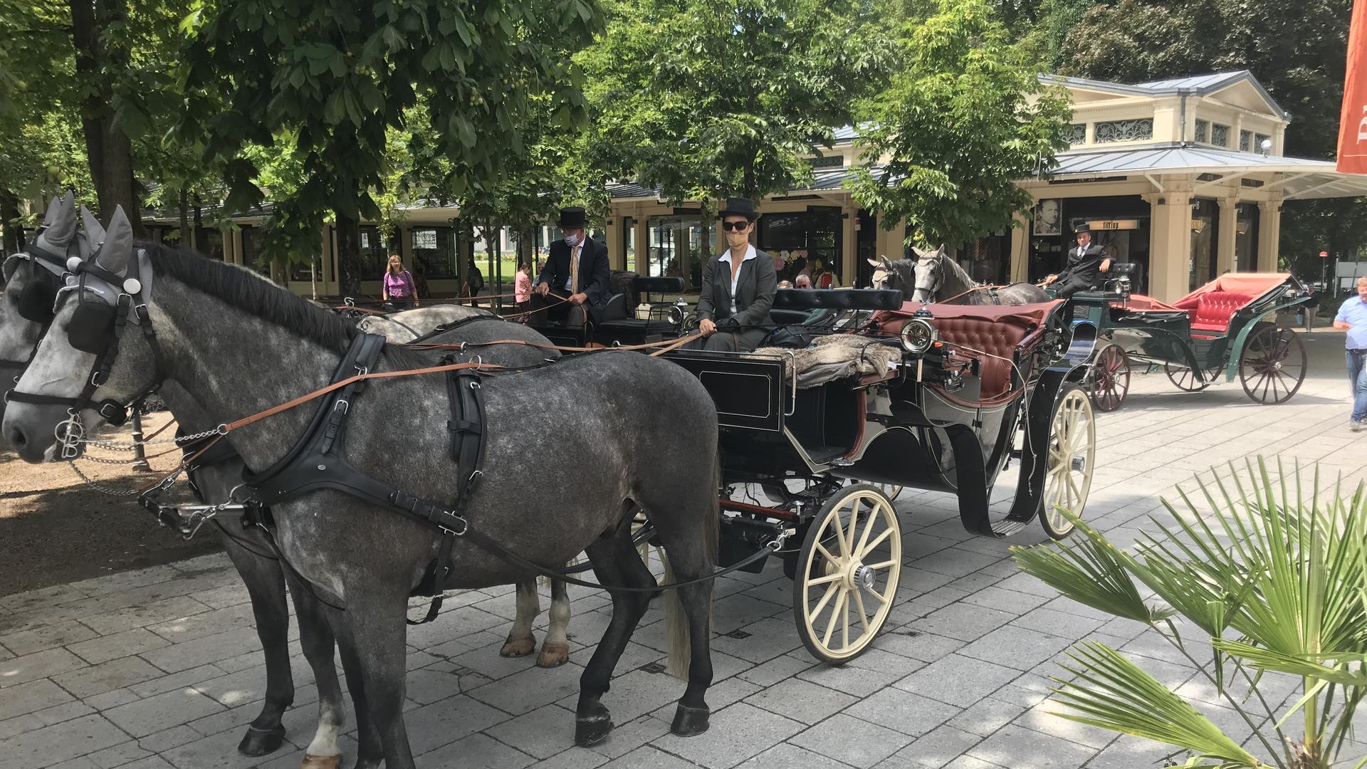 Sabrina Möller, Chefin der Kutschfahrten Baden-Baden, mit ihren drei Pferdekutschen vor den Kurhaus-Kolonnaden