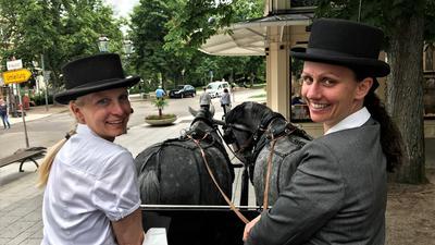 Zwei Frauen sitzen auf dem Bock einer Pferdekutsche.