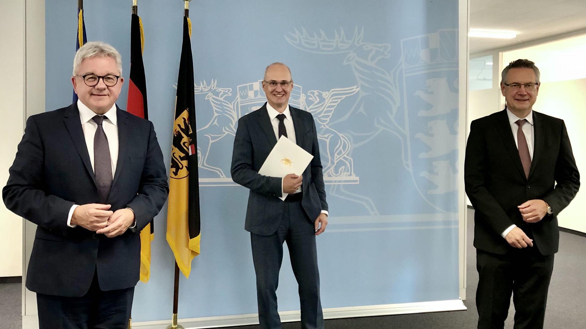 Drei Männer stehen im Justizministerium in Stuttgart. Justizminister Guido Wolf hat dem neuen Landgerichtspräsidenten Frank Konrad Brede die Ernennungsukrunde übergeben. Mit dabei: Alexander Riedel, Präsident des Oberlandesgerichts Karlsruhe.