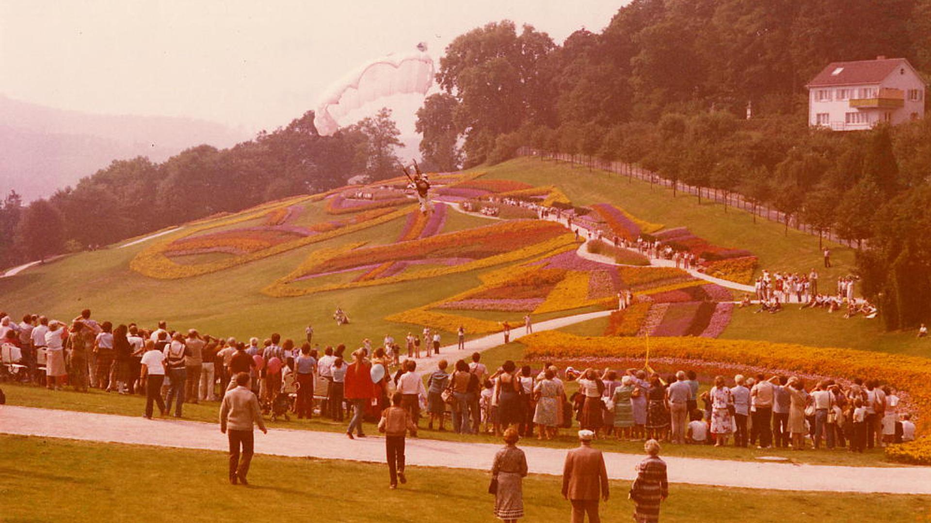 Menschen stehen vor einem Blumenbeet.