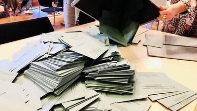 Eine Urne mit blauen Umschlägen mit Stimmzetteln von Briefwählern wird in einem Briefwahlbezirk im Rathaus Baden-Baden auf einen Tisch geleert.
