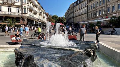 Viele Menschen tummeln sich auf einem Platz mit Brunnen.