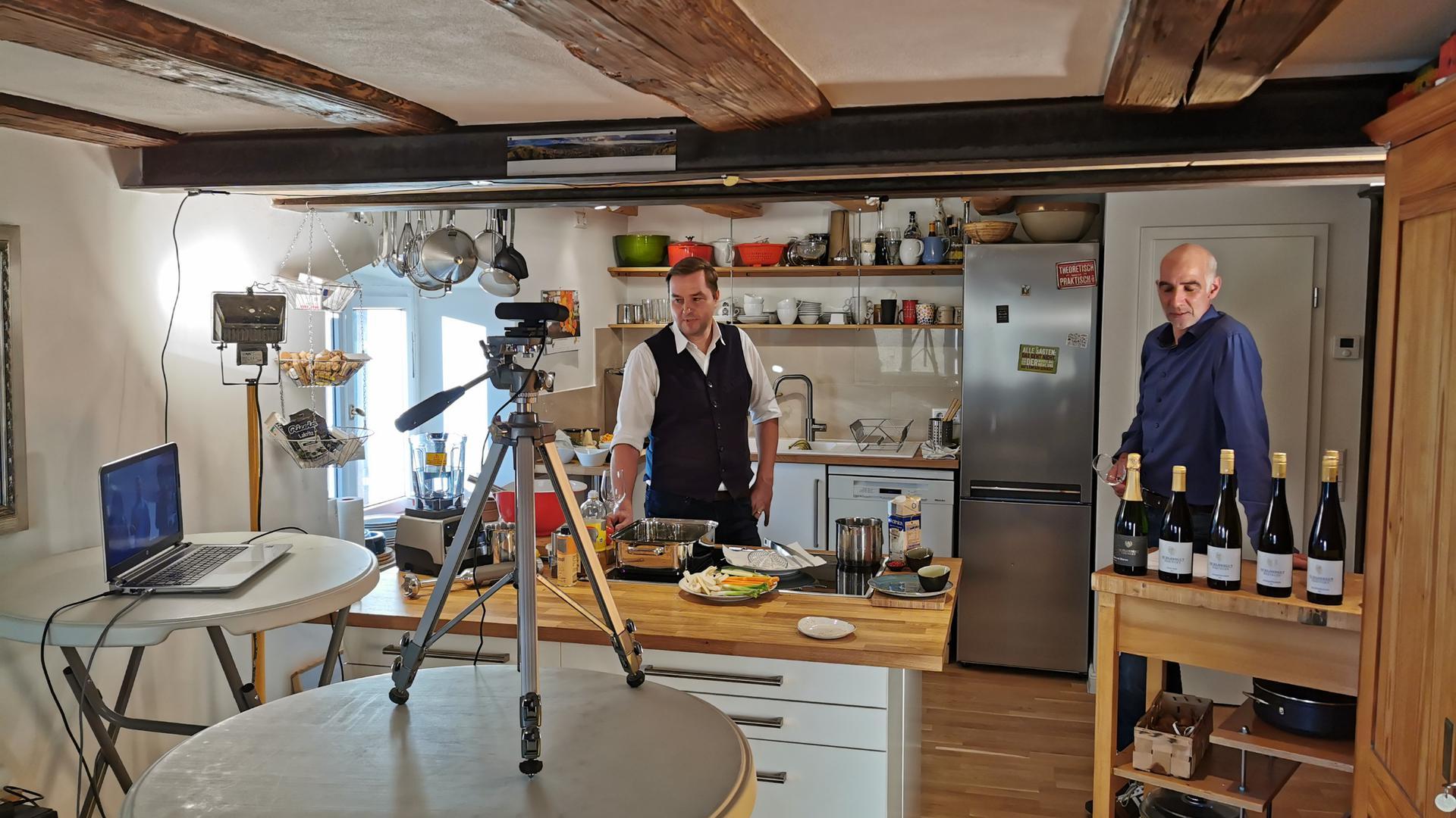 Zwei Männer stehen in einer Küche. Einer bereitet das Essen am Herd zu, der andere steht mit korrespondierenden Weinen bereit.