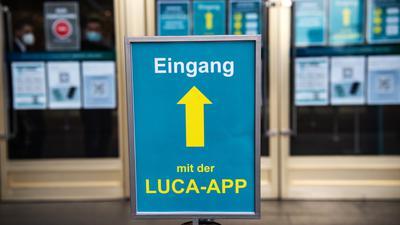 """Ein blaues Schild mit einer gelben Aufschrift """"Eingang mit der Luca-App"""" steht vor einem Türeingang eines Gebäudes."""