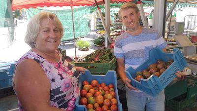 Zwei Menschen stehen mit Tomaten vor ihrem Markststand in Baden-Baden.