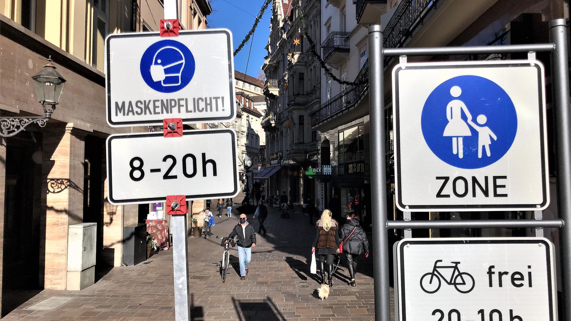 Ein Schild weist auf die Maskenpflicht in der Fußgängerzone Baden-Baden hin.