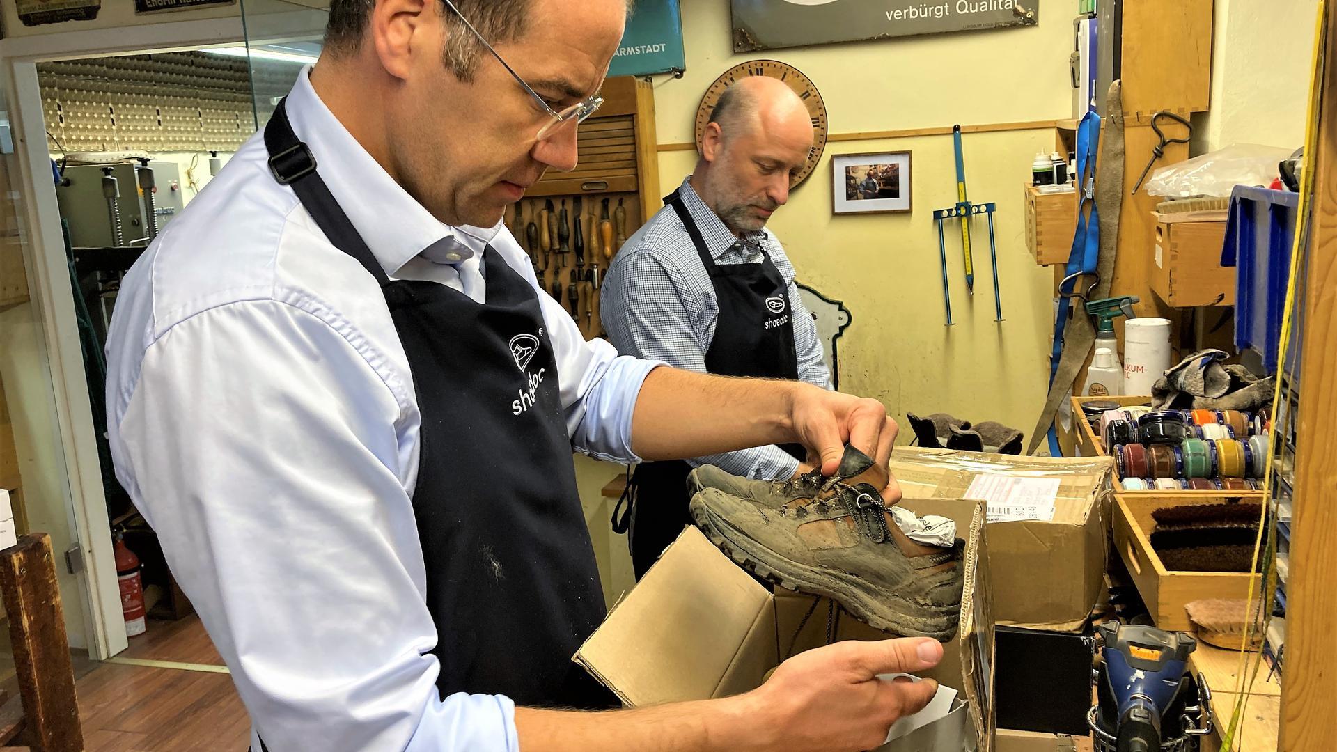 Ein Mann holt ein paar verschmutzte Schuhe aus einem Postpaket.