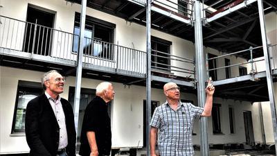 Drei Männer stehen vor einem Neubau.