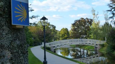 Blaues Schild an einem Baum neben einem Weg an einem Fluss entlang, über den eine weiße Brücke führt