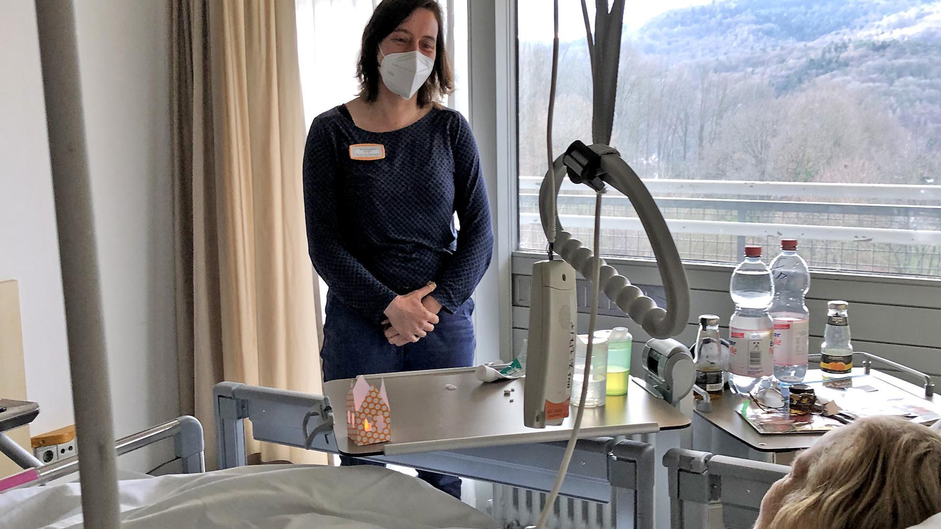 """Mit Abstand und Maske im Patientenzimmer: Pfarrerin Mirjam Keim begleitet eine Patientin in der Klinik in Baden-Baden-Balg und leistet ihr seelsorgerlichen Beistand in der Ausnahmesituation """"Krankenhaus""""."""