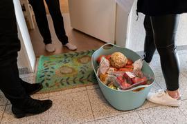Zwei Menschen stehen im Hausflur, während eine Person in der Wohnung steht. Zwischen ihnen steht ein Einkaufskorb mit Lebensmitteln.