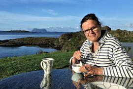 Eine Frau sitzt mit einer Kaffeetasse in der Hand auf einer Terrasse einer Insel in Norwegen