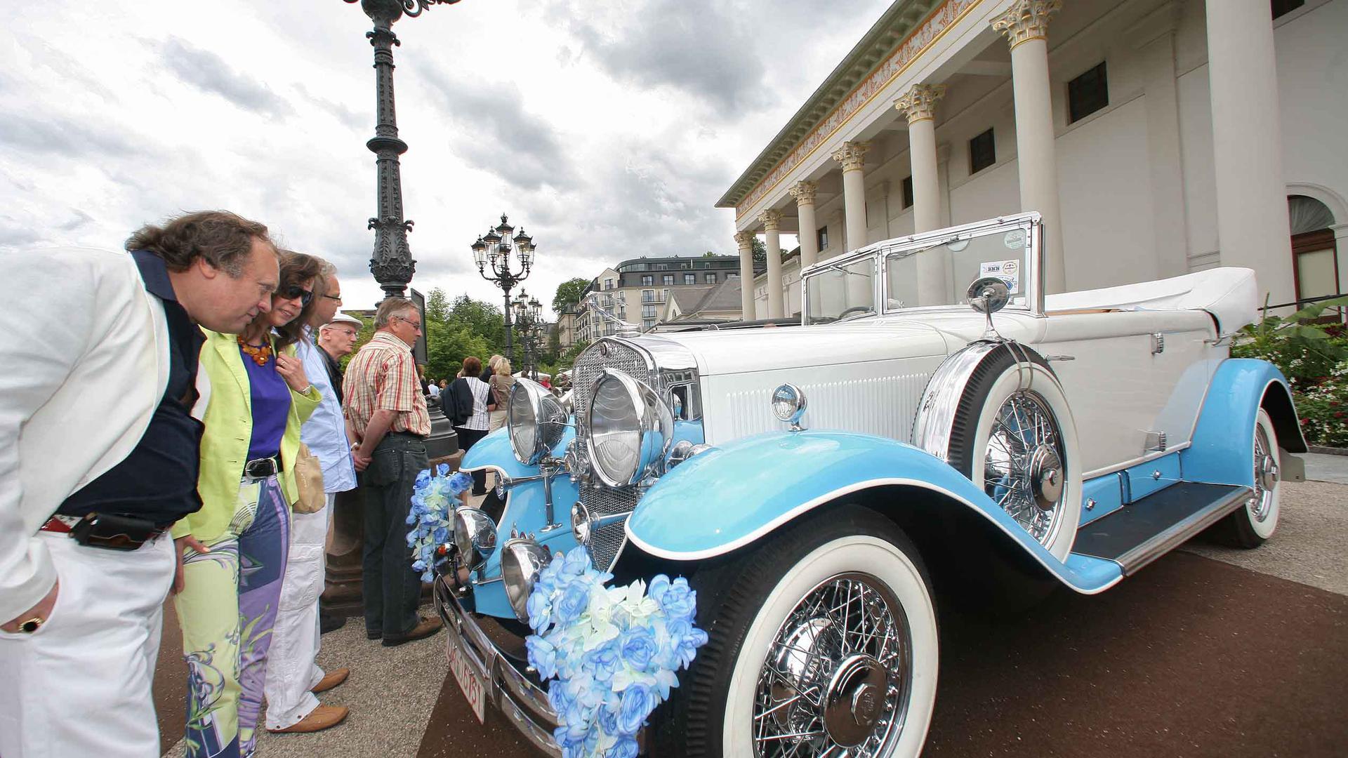 Besucher des Oldtimer-Meetings Baden-Baden bewundern vor dem Kurhaus einen Automobil-Klassiker.