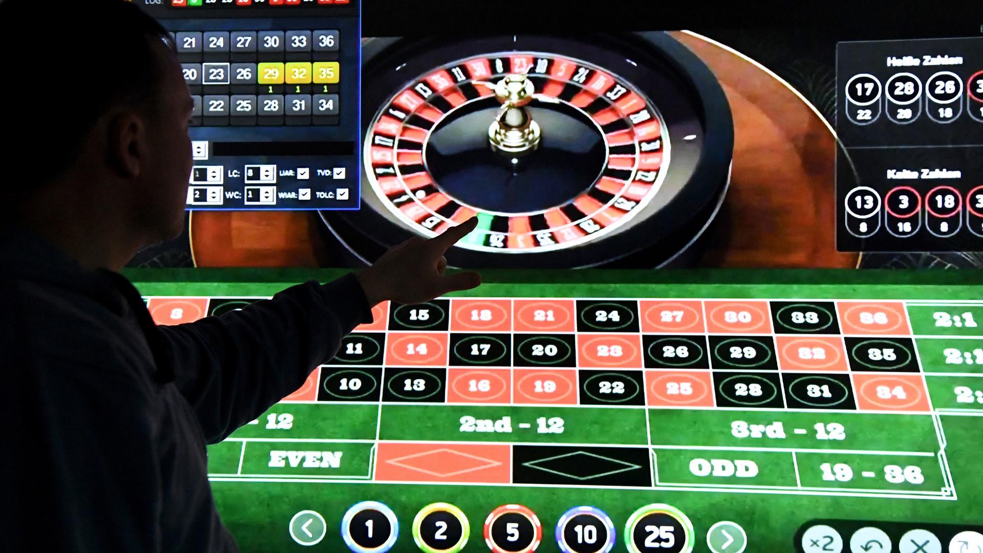 Seorang pria berdiri di depan layar dengan halaman untuk roulette online.