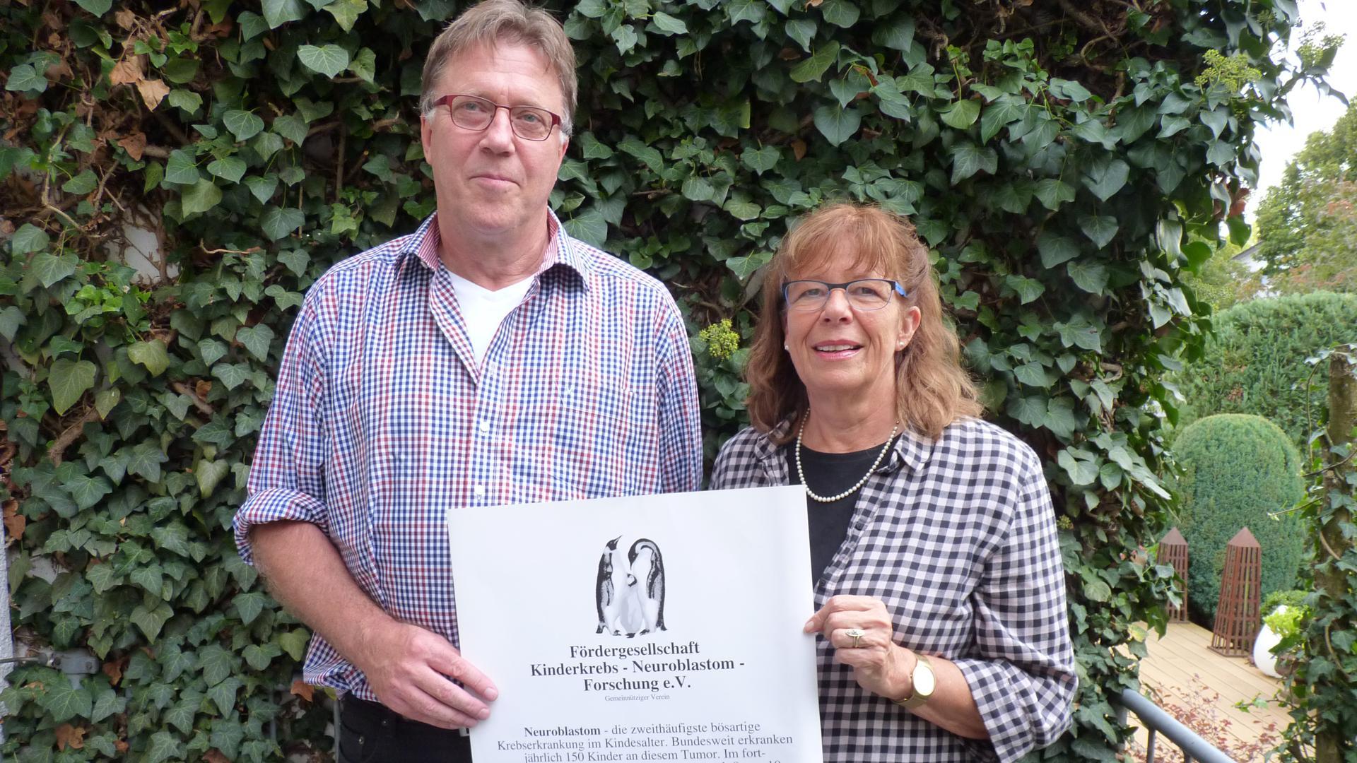 Das Ehepaar Markus und Ulrike Schuster präsentiert ein Plakat.