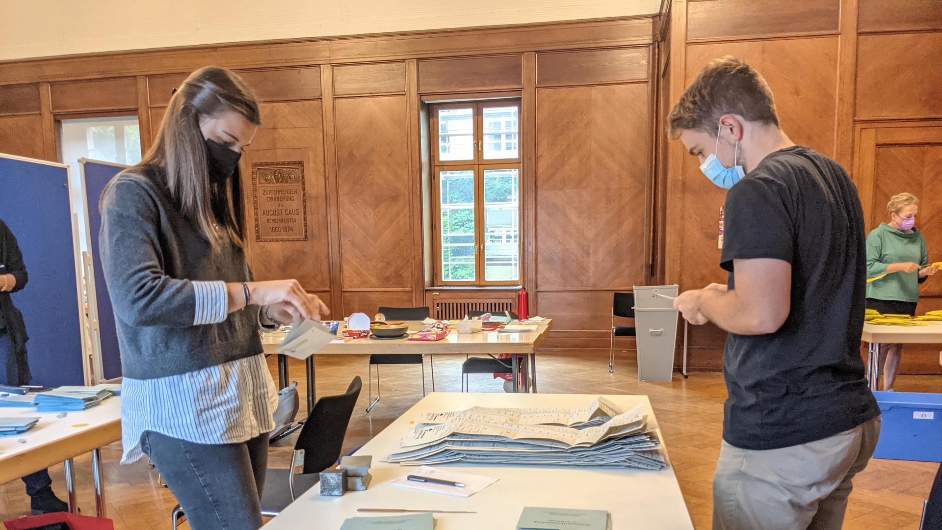 Zwei Wahlhelfer zählen die Stimmen der Briefwahl aus.