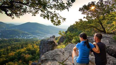 Ein Paar genießt auf den Battertfelsen, die am Panoramaweg liegen, die Sicht auf Baden-Baden bis ins Rheintal hinein.