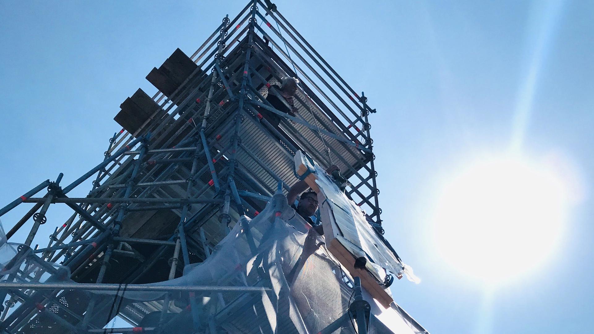 Auf der eingerüsteten Turmspitze der Stiftskirche Baden-Baden wird die Wetterfahne an einem Seil hochgezogen, um sie nach einer umfassenden Restaurierung wieder in über 60 Meter Höhe zu montieren.