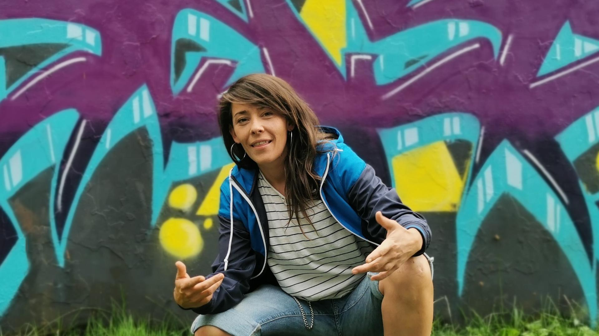 Frau sitzt in der Hocke vor einer Graffiti Wand.