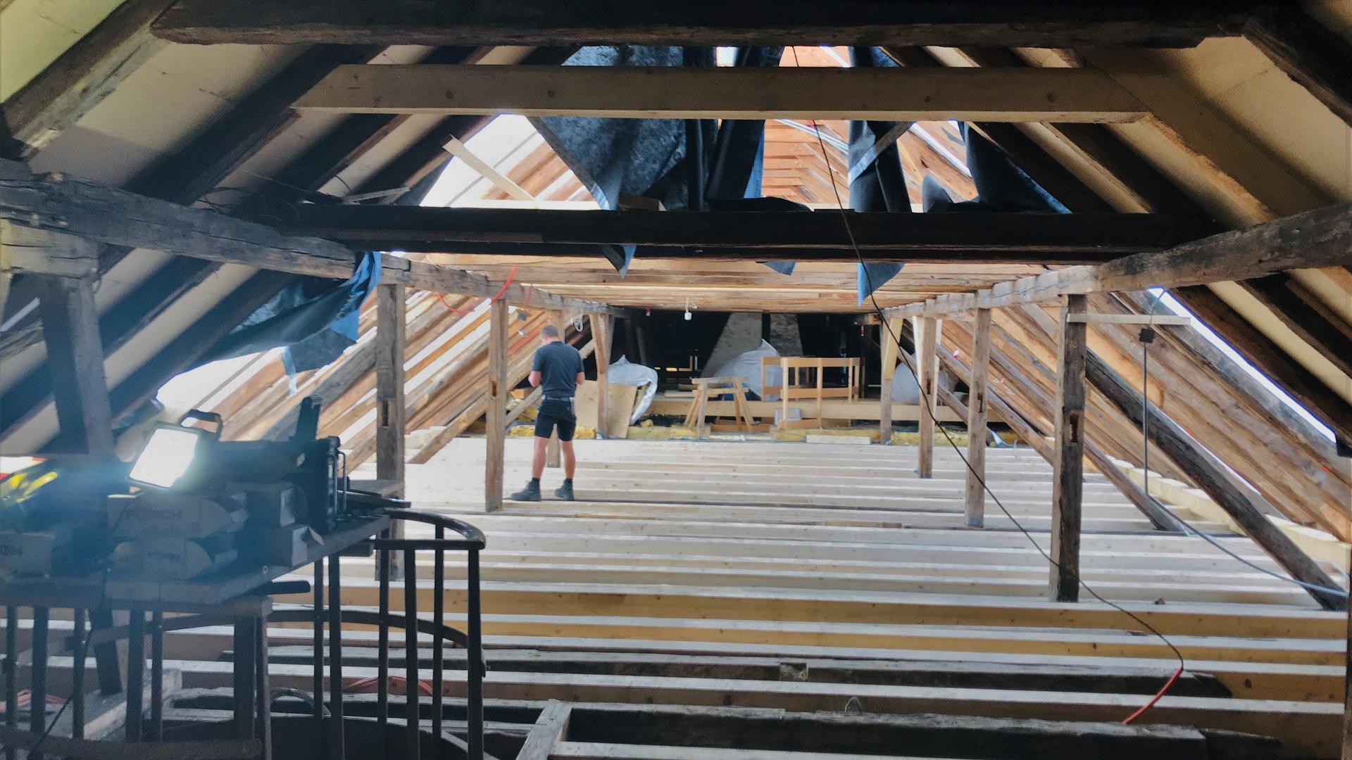 Im historischen Dachstuhl des denkmalgeschützten Rathauses in Baden-Baden sind Handwerker im Einsatz.