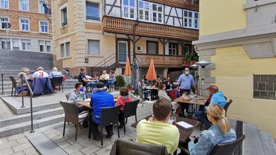 Menschen sitzen auf der Außenterrasse eine Restaurants.