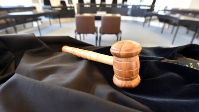 ARCHIV - ILLUSTRATION - Auf einem Tisch im Schwurgerichtssaal im Landgericht Karlsruhe (Baden-Württemberg) liegt am 02.09.2014 ein Richterhammer aus Holz, darunter liegt eine Richterrobe. (zu dpa: «Urteil im Karlsruher Prozess wegen versuchten Mordes erwartet» vom 20.01.2017) Foto: Uli Deck/dpa +++(c) dpa - Bildfunk+++   Verwendung weltweit