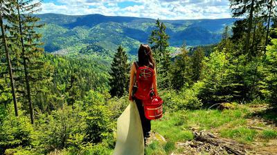 Frau steht vor Aussicht in der Natur und hält Plastikplane fest. Ein roter Eimer baumelt an ihrem Rucksack.