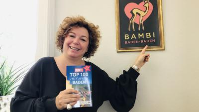 Die Baden-Badener Tourismuschefin Nora Waggershauser steht in ihrem Büro vor dem gerahmten Bambi-Plakat.