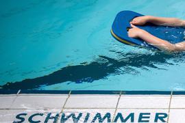 Ein Schüler schwimmt zum Start mit einer Schwimmhilfe durch ein Schwimmbecken.