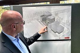 Ein Mann zeigt auf eine Planskizze.