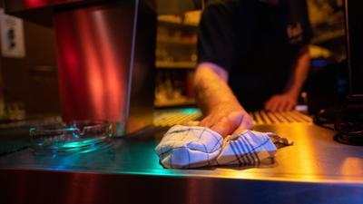 Ein Kellner wischt kurz nach der coronabedingten Sperrstunde den Tresen im Cafe Weiß. Die Landeshauptstadt Baden-Württembergs verbietet wegen der hohen Corona-Zahlen seit Donnerstag den Betrieb von Gaststätten zwischen 23 und 6 Uhr.