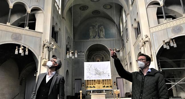 Zwei Männer stehen in einer Kirche. Einer zeigt mit der Hand nach oben.