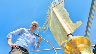 Michael Teipel, Pfarrer der Seelsorgeeinheit Baden-Baden, steht auf einem Gerüst auf der Spitze des Turms der Stiftskirche. Dort wurde soeben die neu vergoldete und restaurierte Petrus-Figur wieder als Wetterfahne montiert.