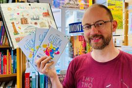 """Buchhändler Josua Straß zeigt in seinem Laden Exemplare seines Buches """"Unsere Glücksmomente - Geschichten aus Baden-Baden""""."""