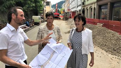 Drei Menschen halten einen Plan.