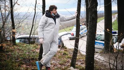 """Schauspieler Hans-Jochen Wagner steht Dreharbeiten zum Schwarzwald-Tatort """"Das Geständnis"""" in einem weißen Schutzanzug im Wald."""