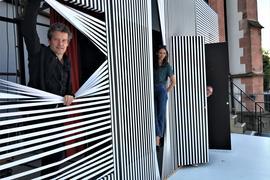 Zwei und ein Frau blicken aus einem schwarz-weiß gestalteten Vorhang.