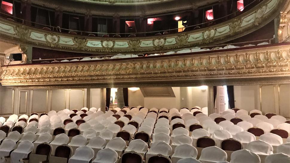 Viele Stühle im Zuschauerraum des Theaters Baden-Baden tragen weiße Hussen. Diese Plätze müssen leer bleiben.