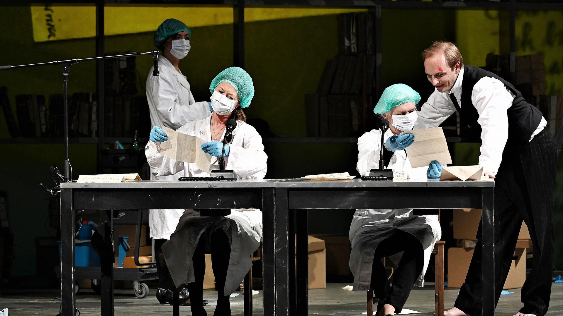 """Mehrere Schauspielerinnen mit Mund-Nasen-Schutz sitzen in dem Stück """"Der Fall Hau"""" des Theaters Baden-Baden an einem Tisch auf der Bühne."""