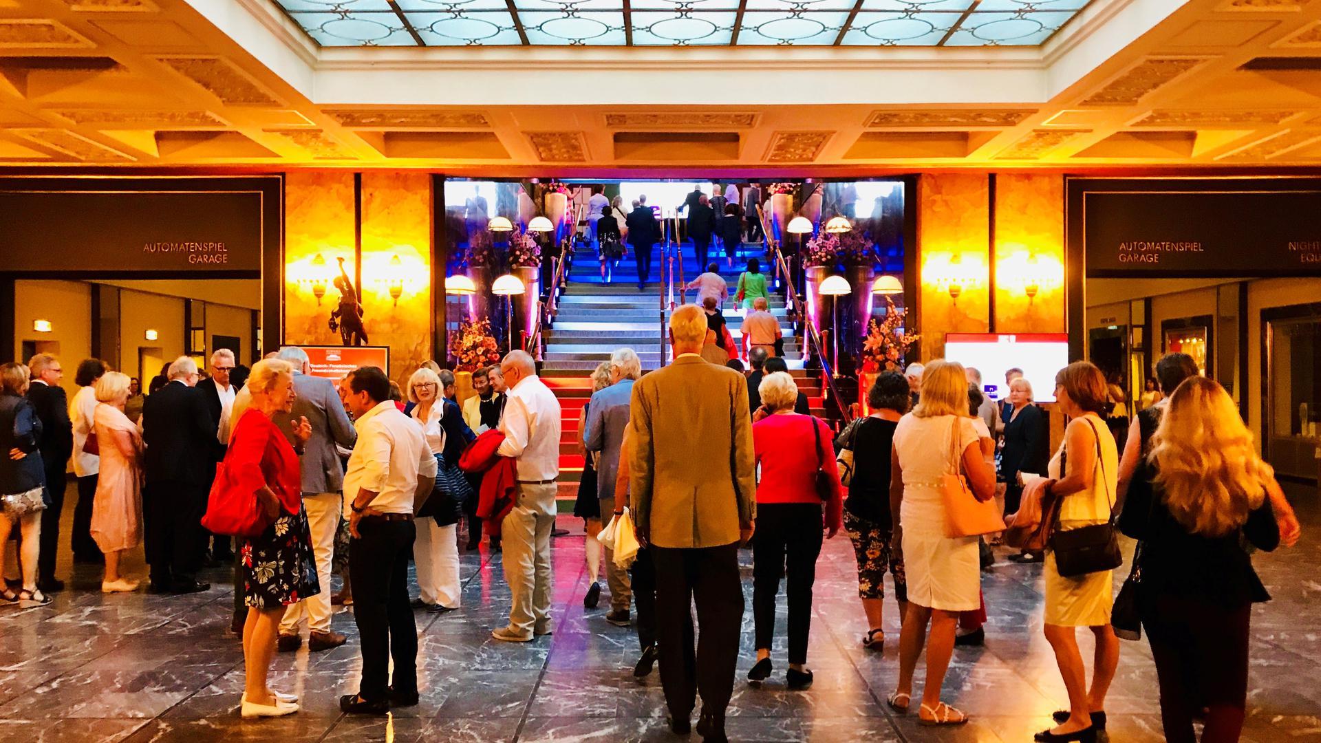 Vor einer Veranstaltung stehen Gäste im Foyer des Kurhauses in Baden-Baden.