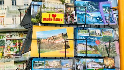 In einem Ständer liegen Postkarten mit Motiven von Baden-Baden.