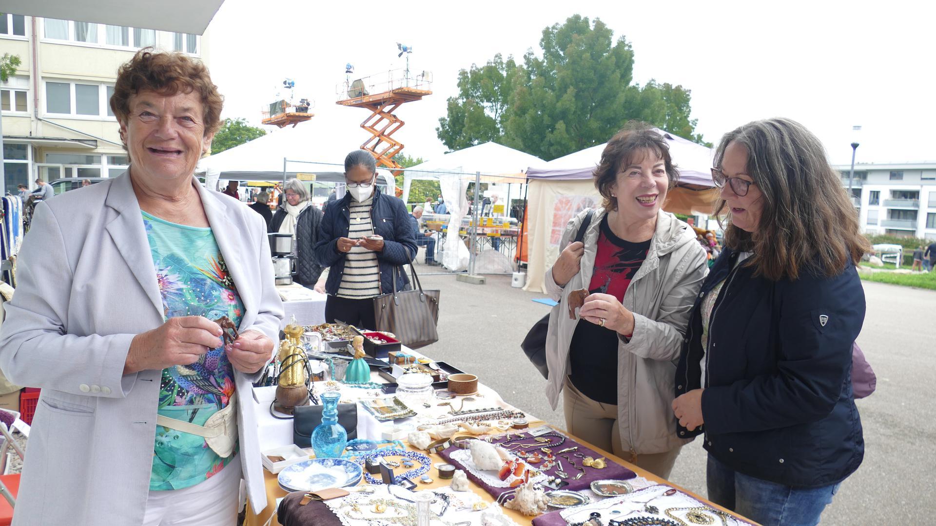 Frauen stehen an einem Stand auf einem Trödelmarkt.