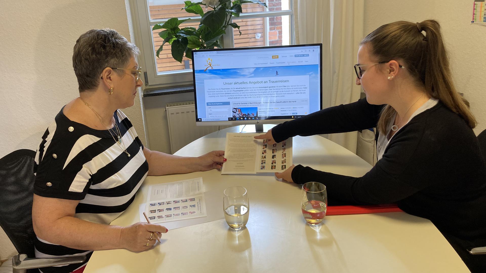 Zwei Frauen an einem Schreibtisch mit Bildschirm