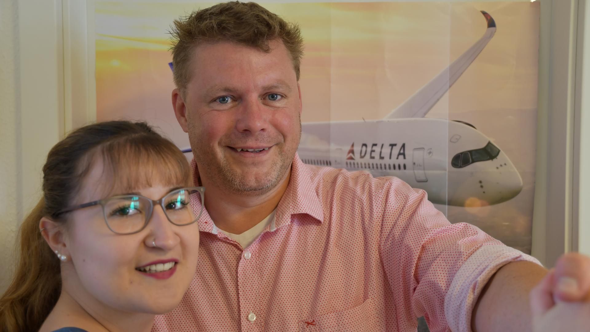 Der Inhaber eines Reisebüros tanzt mit seiner Auszubildenden. Im Hintergrund hängt das Bild eines fliegenden Flugzeugs.