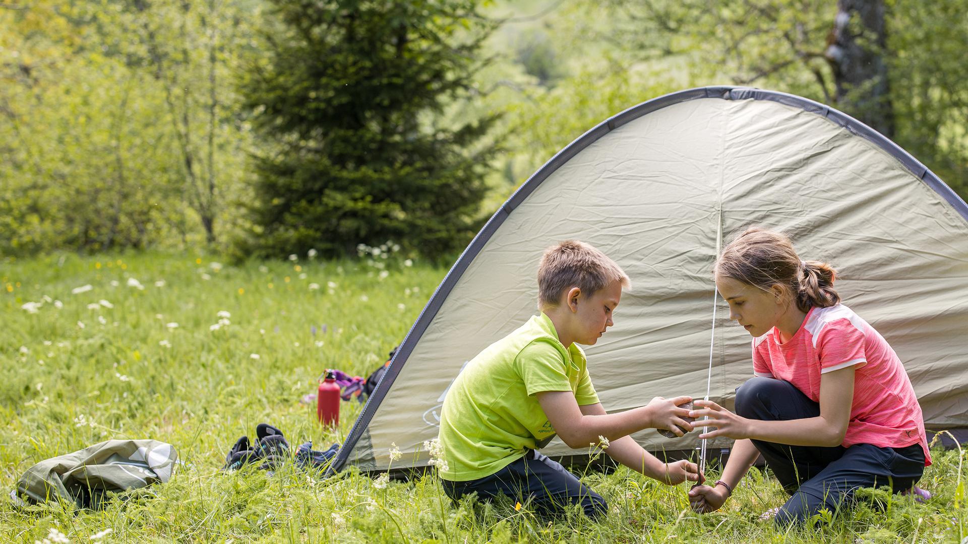 Zwei Kinder spielen auf einer Wiese vor einem Zelt, das in einem Trekkingcamp im Nordschwarzwald aufgebaut ist.