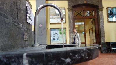Aus einem Brunnen in der Trinkhalle Baden-Baden fließt Wasser.