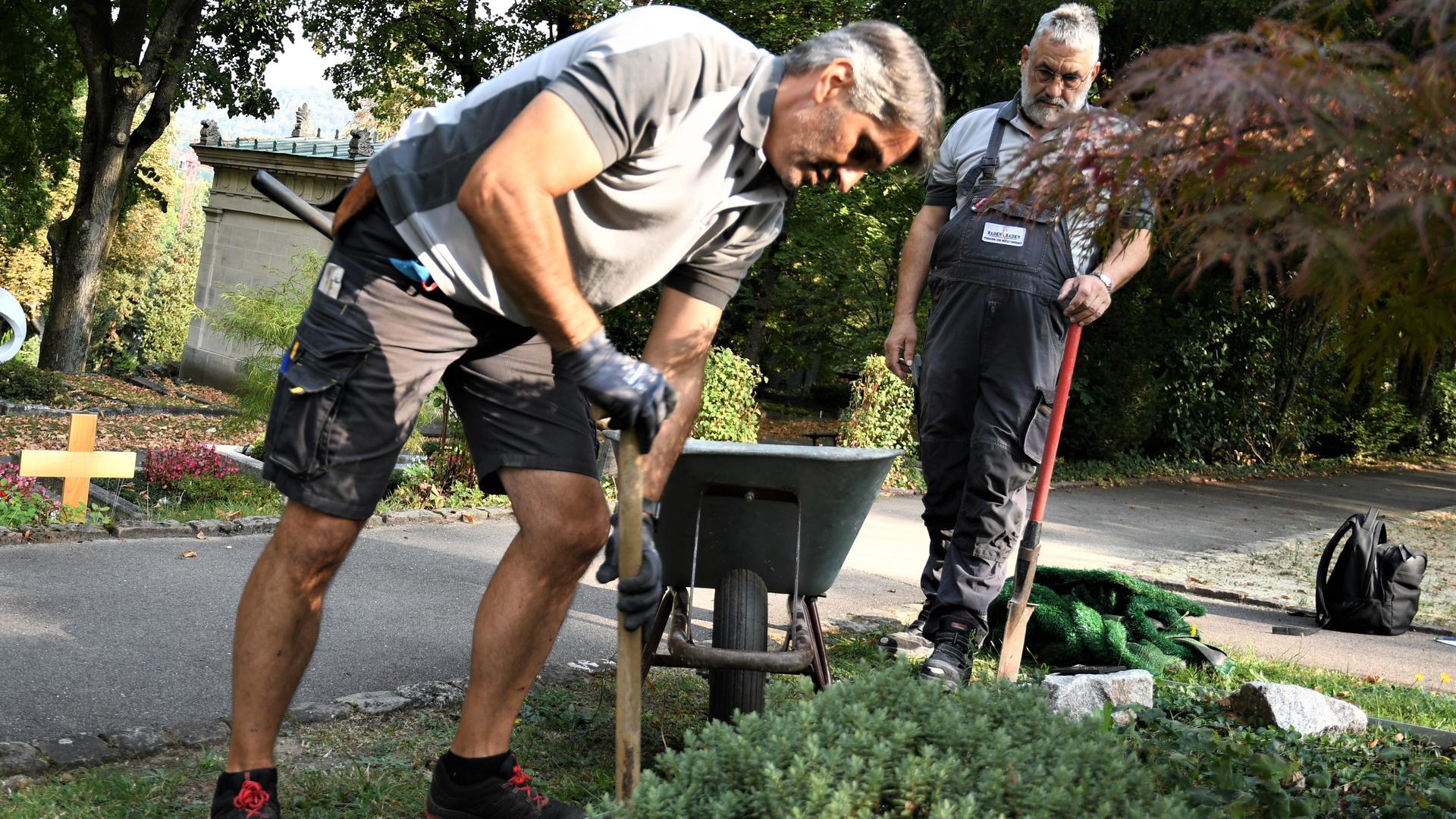 Ein Mann gräbt mit einer Schaufel ein Loch für ein Urnengrab aus.