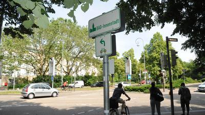 Radfahrer und Fußgänger warten an einer Ampel am Verfassungsplatz in Baden-Baden.